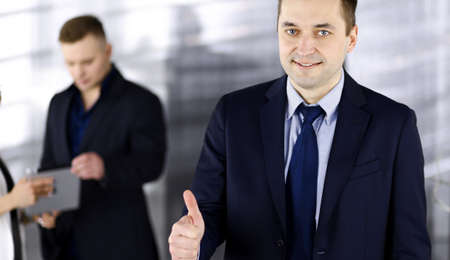 Photo pour Portrait of a successful middle aged businessman, who is enjoying a good result of a teamwork, while standing at meeting in an office. Concept of success in a business - image libre de droit