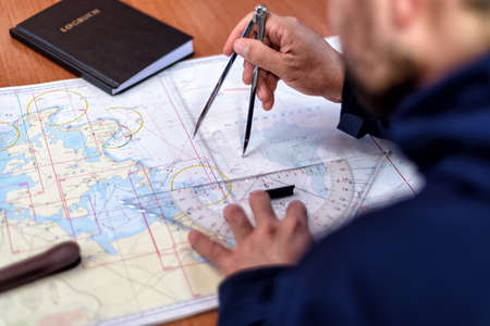 Photo pour navigation with sea charts in the chart room on a sailing yacht - image libre de droit