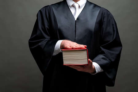 Photo pour german lawyer with a classical black robe, white tie and book - image libre de droit
