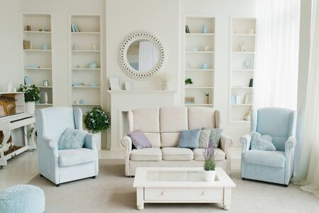 Photo pour Classic living room in blue and white shades. Sofa, armchairs, fireplace, coffee table and mirror in the house - image libre de droit
