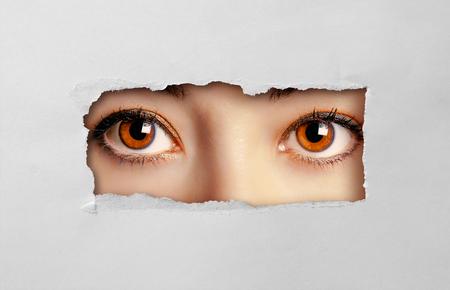 Foto de Beautiful female eyes looking through a hole on cardboard - Imagen libre de derechos