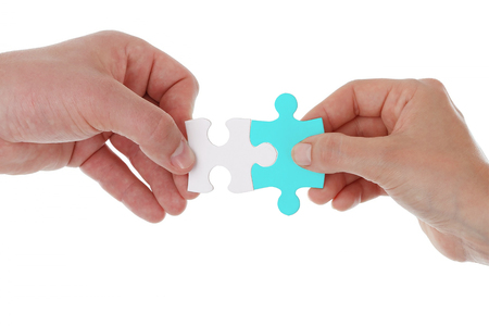 Photo pour Hands holding and joining two pieces of puzzle together isolated on white.Teamwork partnership cooperation and matching concept - image libre de droit