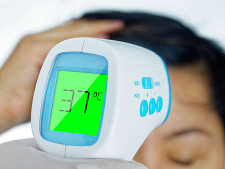 Photo for Hand holding Thermometer Gun Side View Medical Digital Non-Contact Infrared Sight Handheld Forehead Readings woman. Temperature Measurement Device Isolated - Royalty Free Image