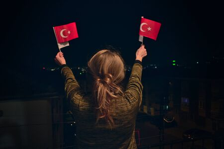 Photo pour Turkish Woman Holding, Waving 2 Turkish Flags at night Celebrating April 23 National Sovereignty Children's Day - image libre de droit