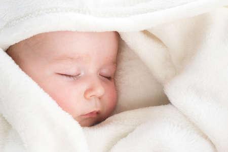 little boy sleeping on soft white blanket