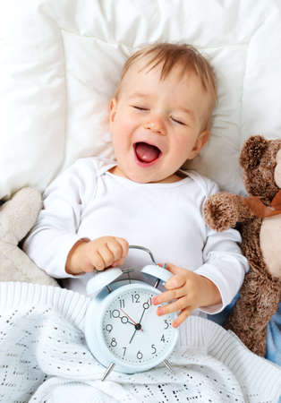 Photo pour One year old baby lying in bed with alarm clock - image libre de droit