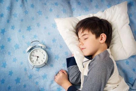 Foto de six years old child sleeping in bed on pillow with alarm clock - Imagen libre de derechos