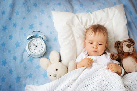 Foto de One year old baby lying in bed with alarm clock - Imagen libre de derechos