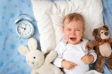 Foto de One year old baby lying in bed with alarm clock and crying - Imagen libre de derechos