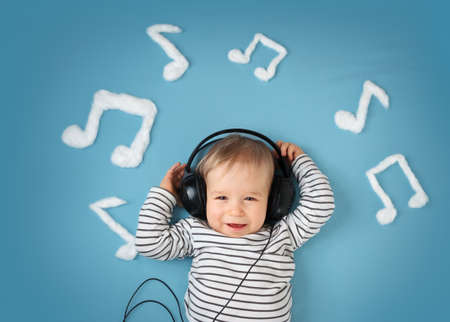 Photo pour happy little boy on blue blanket background with headphones and musical notes on blue background - image libre de droit