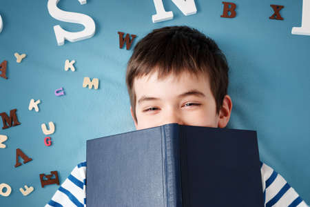 Photo pour seven years old child lying with book and letters on blue background - image libre de droit