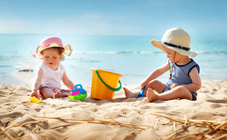 Photo pour Babygirl and babyboy sitting on the beach in straw hats - image libre de droit