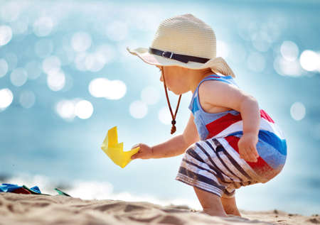 Photo for one year old boy playing at the beach in straw hat. Child with a paper ship at sea - Royalty Free Image
