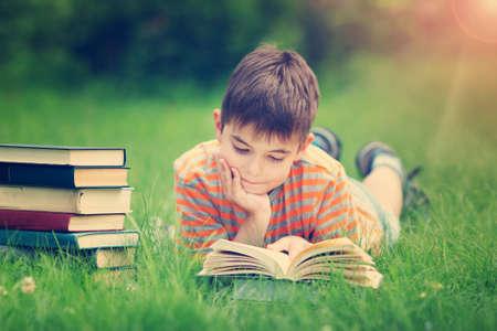 Foto de seven years old child reading a book lying on the grass - Imagen libre de derechos