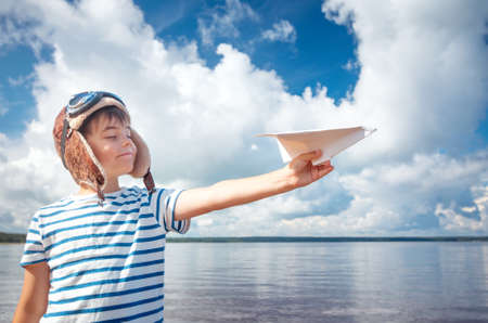 boy playing with a paper plane in aviator hat