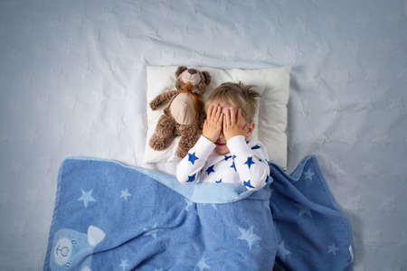 Photo pour Three years old child crying in bed. Sad boy on pillow in bedroom - image libre de droit
