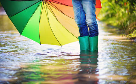 Photo for Child walking in wellies in puddle on rainy weather. Boy holding colourful umbrella under rain in summer - Royalty Free Image