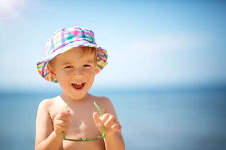 Photo pour little boy smiling at the beach in hat with sunglasses - image libre de droit