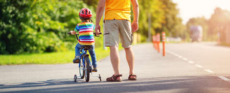 Photo for a child on a bicycle in helmet with father on asphalt road - Royalty Free Image