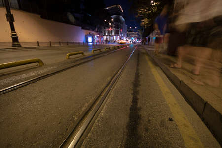 Photo for Tram rails on asphalt. People walking and traffic lights on the sidewalk. Filmed at night with long exposure. - Royalty Free Image