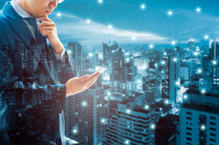 Photo pour Double exposure of professional businessman connected internet and wireless network with his smart phone and city of business background in business trading and technology concept - image libre de droit