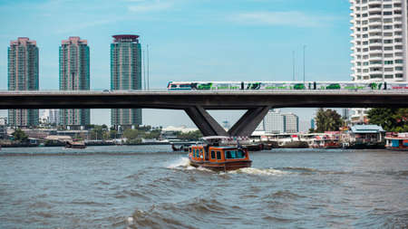 Boats on the river and the train tracks and buildings in the city center of Thailand