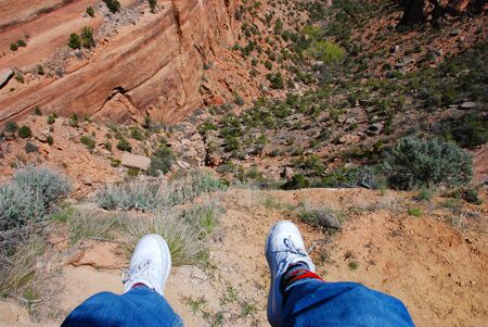 Dangling feet far above the bottom of Ute Canyon in Colorado National Monument