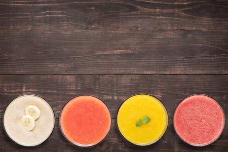 Set of fruit smoothie and juice in glasses on wooden background with a lot of copy space for your text or editing.の写真素材
