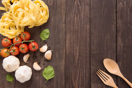 Pasta ingredients. tomato, garlic, pepper and mushroom on wooden background.