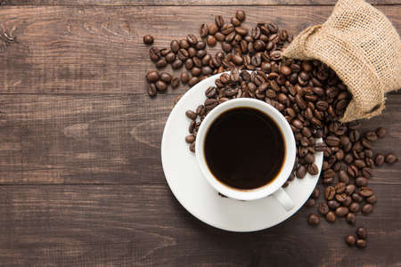 Photo for Coffee cup and coffee beans on wooden background. Top view. - Royalty Free Image