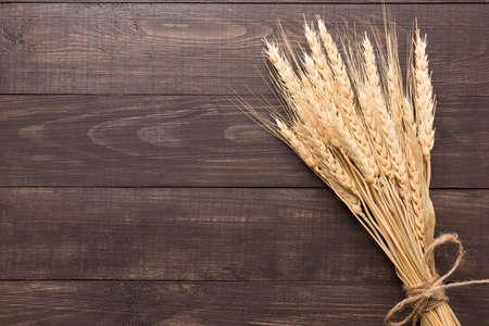 Photo pour Wheat ears on the wooden background. Top view. - image libre de droit