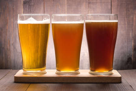 Assortment of beer glasses on a wooden table.