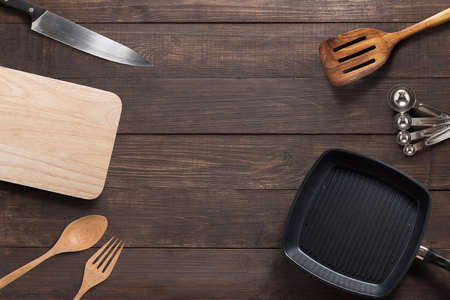 Various kitchenware utensils on the wooden background.