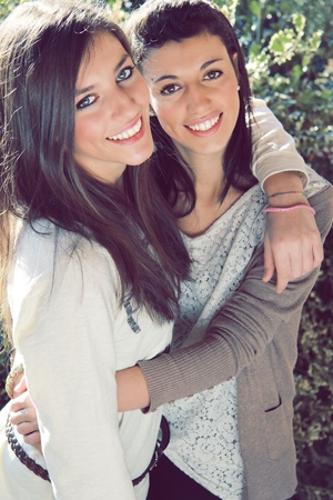Two young smiling sisters embraced   Outdoor and natural light