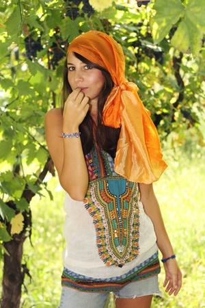 Beautiful girl in a vineyard eats a grapeberry dressed like a gypsy
