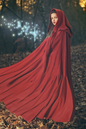 Beautiful woman with red flying cloak posing in the woods