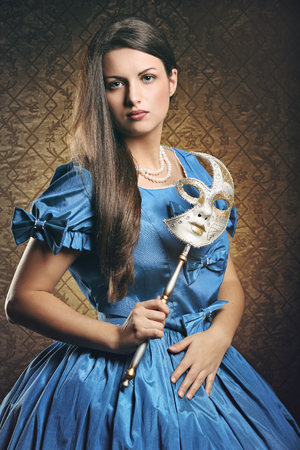 Beautiful woman in blue historical dress with venetian mask . Venice carnival portrait