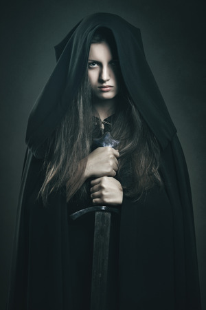 Beautiful dark woman with black robe and sword . Fantasy and legend