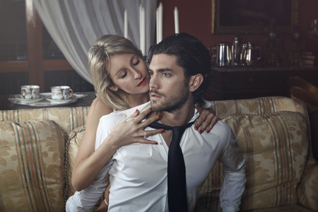 Seductive woman undressing elegant handsome man. Valentine day celebration