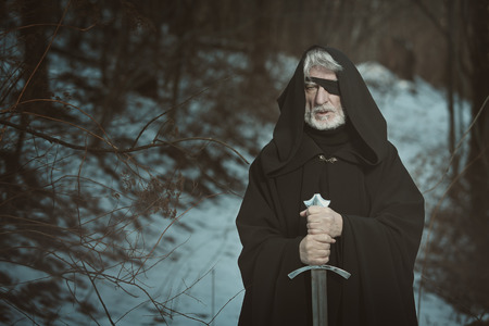 Old one eyed man with sword in a dark forest . Fantasy and mythology