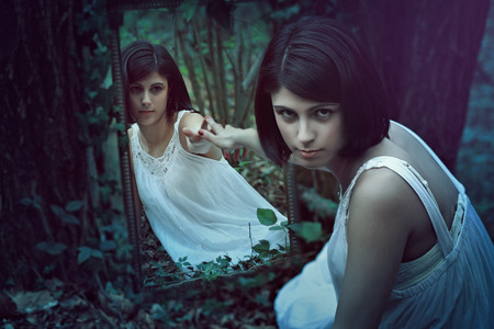 Beautiful pale woman in a dark forest with a strange mirror. Surreal and weird