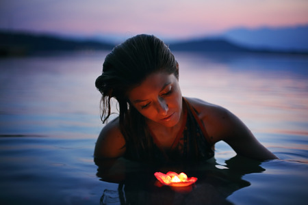 Beautiful woman with floating candle in purple lake waters . Beauty and romance concept