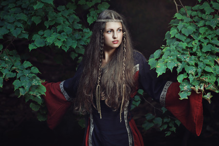 Portrait of a medieval young lady among forest tree . Historical and fantasy