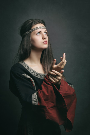 Beautiful woman in medieval dress praying with eyes to the sky. Historical and religion