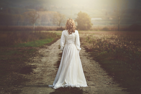 Foto de Bride with beautiful dress in country fields. Purity and innocence - Imagen libre de derechos