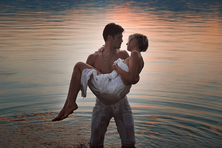 Romantic couple in lake waters at sunset. Love and tenderness