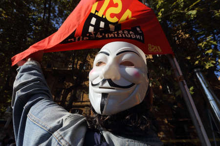 Foto per Rome, Italy - October 18, 2019: The mask of Anonymous in front of the flag of Asia USB during the garrison in front of the ministries - Immagine Royalty Free