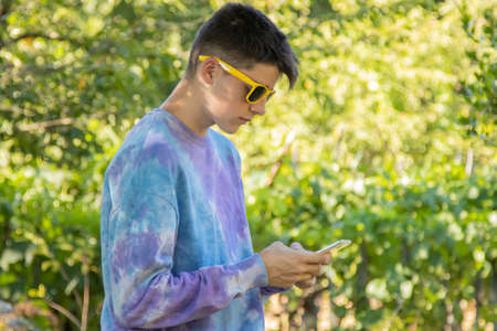 Photo pour young teenager in the field with mobile phone - image libre de droit