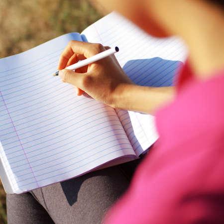 Girl writing in notebook in a field.