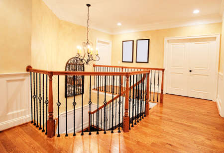 Interior of an upscale home, showing the upper hallway and top of the staircase. Horizontal format.